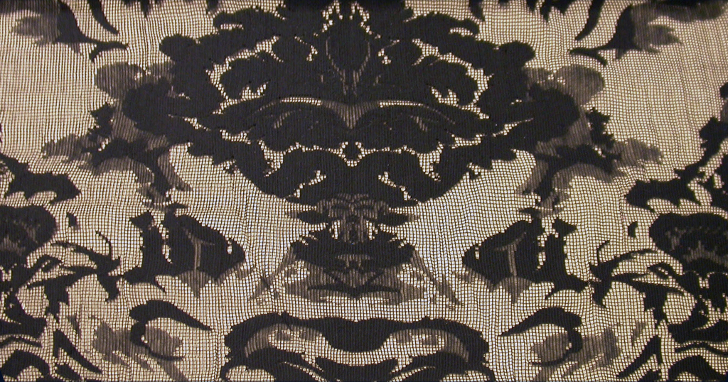"Black lace with a vertically symmetrical ""urn and flowers"" style pattern, where the urn is replaced by the face of the devil, and the cherubs by tiny demons."