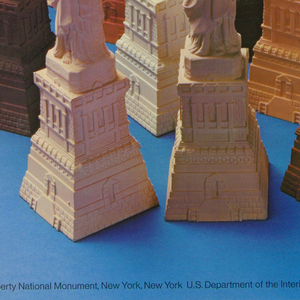 An assortment of Statuettes of the Statue of Liberty in various colors representing the diverse ethnic groups that have immigrated to the United States.  Placed against a blue background, the torches are pointing up toward white letters above each statue. The text reads: Visit the / American / Museum of / Immigration / at the / Statue / of Liberty /. Around the edge of the poster is a white border.