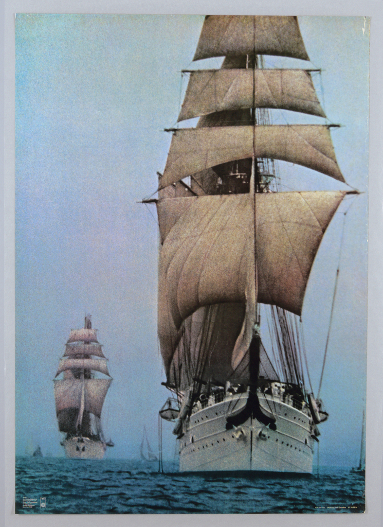 Color photographic reproduction of two tall ships under full sail. Large ship at right fills the sheet with smaller ship in the middle distance at left. Accompaning sailboats at lower left, right and center. Texture of the image is grainy.