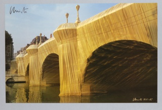 Color photographic image of the wrapped Pont Neuf in Paris. The bridge is strongly lit in the afternoon sun which contrasts with the large shadowy areas under the bridge.  The bridge is depicted on a strong diagonal across the sheet from left to right with reflections in the water at left and large, dark arches on the right.