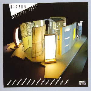 """Photographic reproduction of an interior view of a designer's showroom area. Featured are brightly lit and colorfully designed wall screens and room dividers.  The arrangement is set on an irregular platform and surrounded by darkness. At upper left corner a white triangle jutts into the image with black letters """"DIAFOS,"""" and below """"MATERIAL LIGHTS."""" Across lower edge of sheet from left to right  the names of the lighting/furniture designers featured."""