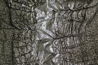 Length of metallic silver and black fabric with a variably puckered surface that resembles the skin of a crocodile.