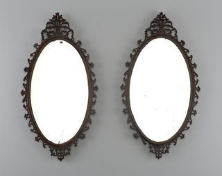 In George III style, each oval mirror with open-work frame having palmette crest at top.