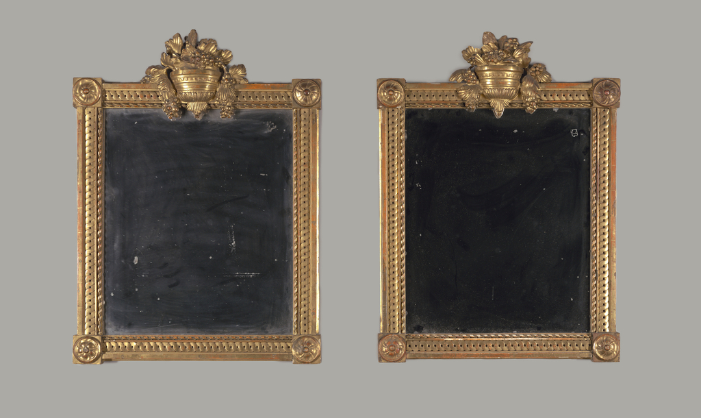 In Louis XVI style. Each mirror with vertical frame, almost square, carved and gilded with bowl of grapes and grape leaves at center top and a spiral in circle on square at each corner. Frame molding comprised of squared outer band, guilloche band in center and ribbon twisted around rod at inner edge. Mirror in each.