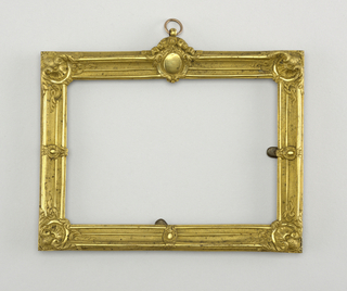 Horizontally oriented rectangular form, shells at the corners and cabochons in the center of each side; small circular ring at top.