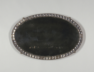 """Oval mirror surrounded by oval metal frame with row of square, faceted glass """"jewels""""; wood backing; four mounting rings on reverse, allowing vertical or horizontal orientation."""