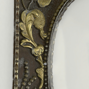Rectangular form with cast scrolling floral and foliate decoration, and cherub mask in lower right corner, all surrounding beaded oval opening; glass panel in opening. Reverse with hanging-ring in top, center.