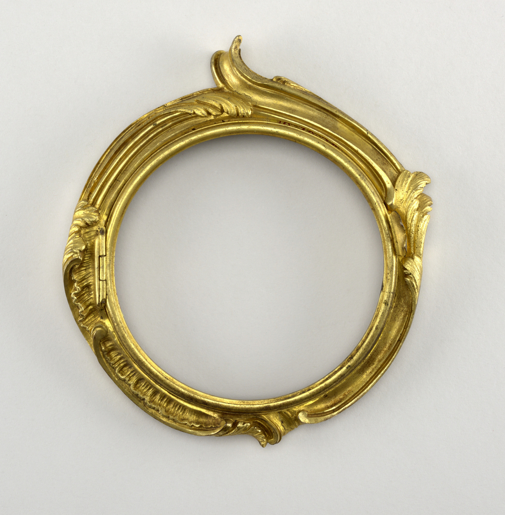 Circular, with large rocaille foliation; hinged circular rim on inner circumference for holding glass. Part of a clock.