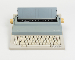 "Low, stepped rectilinear body; top section and paper support in light blue, yellow knobs on left and right ends of platen, and gray base with gray ""QWERTY"" keyboard and function keys. Linear indented banding in base visible in profile."