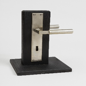 A double-sided block mounted on each side with a narrow cylindrical door handle and rectangular backplate with keyhole.