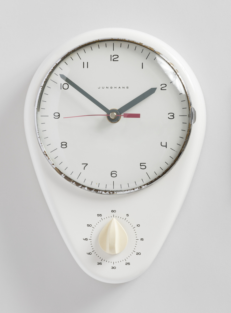 White ceramic housing in inverted teardrop shape with a rounded top and bottom; circular clock dial at top with numerals and minutes marked in black; black strip metal hands with pointed ends; circular timer immediately below clock face, with back numerals against a plain white background,showing five minute intervals form 0 through to 60, with white plastic knob.