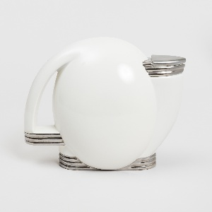 Upright disc-shaped teapot, the spout and handle forming opposing symetircal curves; white ground with silver-colored banded base, spout rim and base of handle; separate triangular lid on spout.