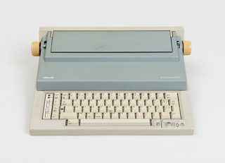 """Low, stepped rectilinear body; top section and paper support in light blue, yellow knobs on left and right ends of platen, and gray base with gray """"QWERTY"""" keyboard and function keys. Linear indented banding in base visible in profile."""