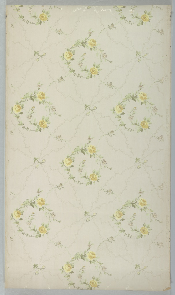 Yellow roses on stems are scrolled and form a circle, with each of these floral wreaths separated by a framework resembling moire. Small floral sprigs are scattered throughout. Printed on light colored ground.