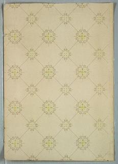 Two alternating roughly circular motifs composed of foliate scrolls with a center floral motif, connected to its adjacent motif by a broken or dashed line. Forms a grid or trellis pattern.