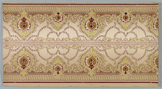 On light gray ground, small and large arabesques in tan containing green and burgundy motifs; scrolls and twists on borders; inside rinceaux. Two borders printed across the width.