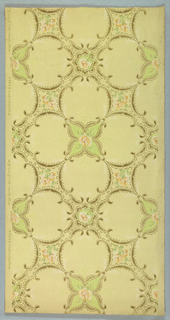 Large trellis pattern of alternating quatrefoils and diamond shapes with concave sides. Both shapes are outlined with foliate scrollwork, and contain large cream-colored blossoms. Faintly rendered, symmetrical sprigs of leaves sprout from points and corners. Pattern is printed in tans and greens on a khaki ground.