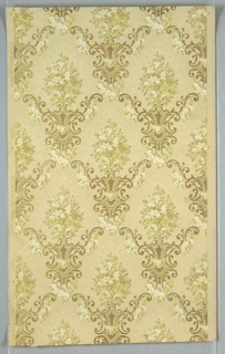 Diaper pattern with shield-like shape at intersection. From this sprouts a floral bouquet. Printed in green, brown, white and metallic gold on tan ground.
