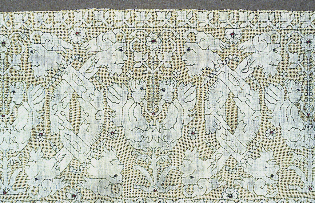 Linen border with silk fringe on one long edge, completely covered with deflected element embroidery in yellow silk. The pattern areas are reserved in the linen ground fabric, along with one long rectangle reserved as if for an inscription. Paired confronted cherubs alternate with interlocking branches terminating in human heads at both ends. All motifs are outined in green silk; black beads for eyes; red beads as centers of rosettes.
