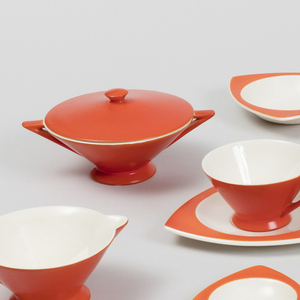 Triangular plates, bowl, cup and saucer, creamer, and sugar bowl, the plates and bowl with curved orange-red rim and circular white well; cup, creamer and sugar bowl of inverted cone shape with triangular handles.