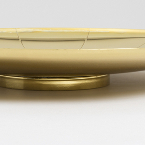 Footed circular tray with narrow rim and two wide strap handles; surface decorated with incised lines radiating from center.