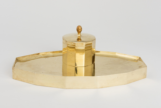 Lozenge-shaped base surmounted by box-like inkwell with hinged lid and removable glass liner.
