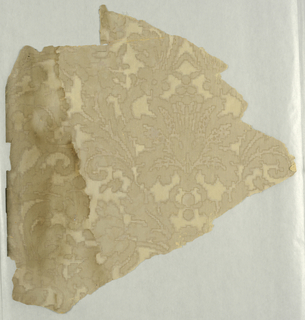 Small stylized floral motif, imitating textile, may possibly be a diaper pattern, printed in beige with darker outline on off-white ground.