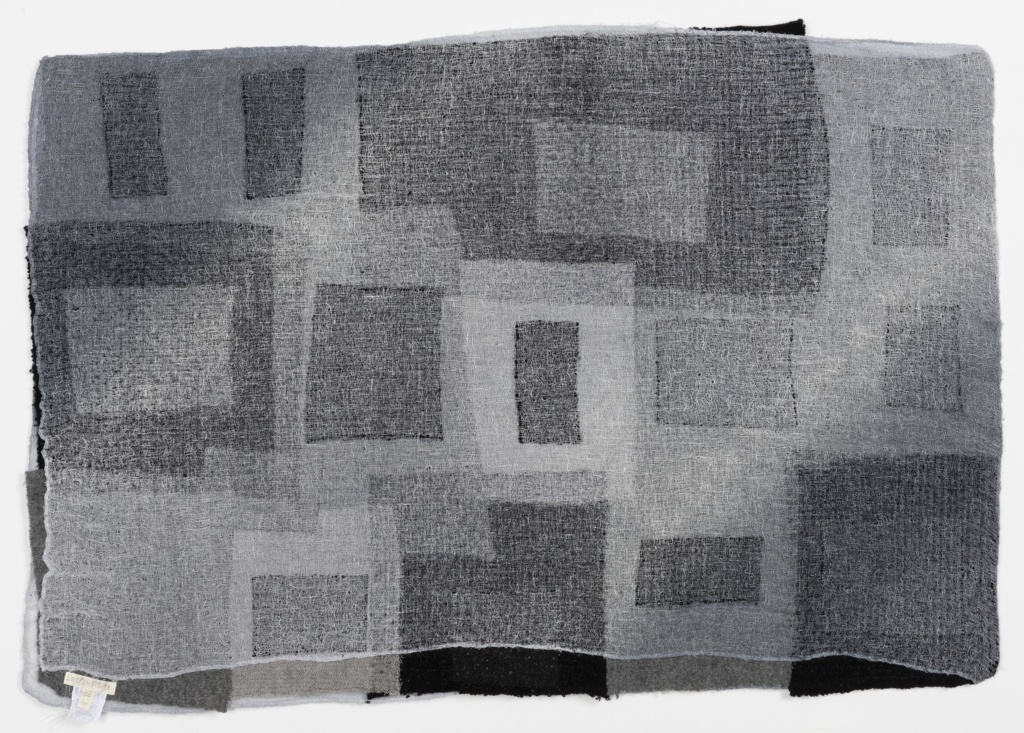 Sample of needle-punch fabric with an abstract design of squares and rectangles in softly blended black, gray and white. Made from recycled Eileen Fisher garments.