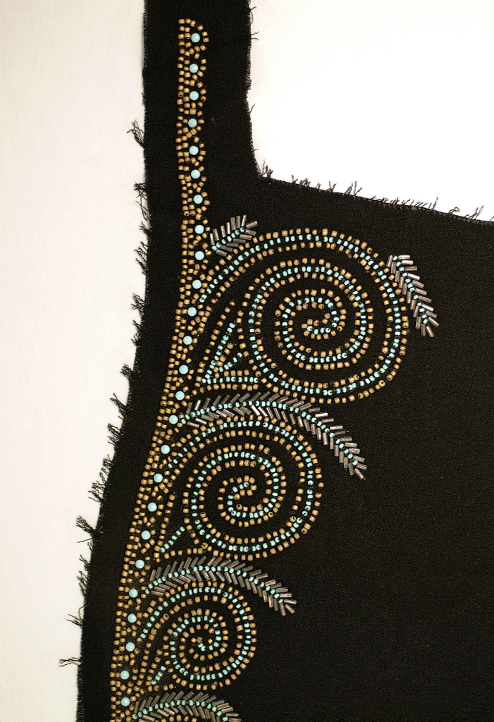 Black crepe with scroll design, beaded with hematite bugle bead, turquoise and gold seed beads, and turquoise enameled studs. 1940s.