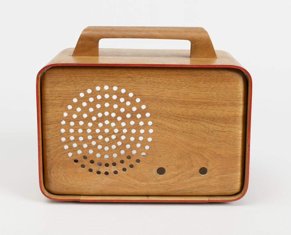 Rectangular plywood form with curved edges and corners; low rectilinear wooden handle on top; face with speaker grill composed of concentric rings of circular holeson left, two holes to receive dials bottom right.