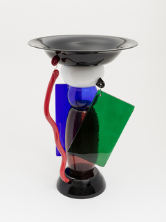 Circular bowl with broad rim on tall base of assembled geometric glass forms of various opaque and transparent colors (blue, purple, red, white), some suspended by brass wire; all on a slightly domed foot of dark glass.