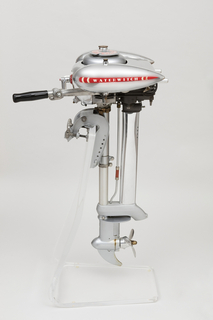 """Aluminum housing with teardrop shaped fuel tanks on left and right, each marked with a red and white decal imprinted """"WATERWITCH""""; projecting tiller with black handle at front; housing sits on rod-like mid-section topped by clamp, and leading to exhaust pipe, and propeller at bottom."""