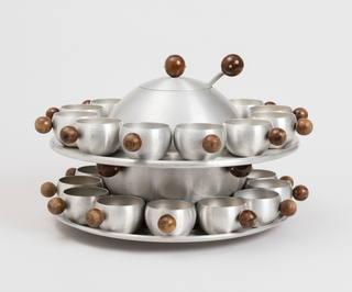 Spherical punch bowl and lid (a,b) with spherical wood finial on lid and four wood spheres on sides of bowl; ladel (c) with spherical wood finial; circular tray (d) rests on punch bowl and holds twelve cups (e/p) with spherical wood handles.