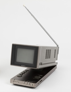 Long rectangular form with square picture tube at front. Housing hinged at back to adjust viewing angle and height, and reveal control buttons and knobs on base; telescoping antenna on side, fits in chanel in housing.