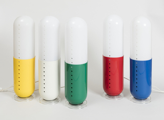Suite of five lamps, each resembling a giant pill, it's upper half a translucent white difuser, its lower half a bright primary color: red, yellow, green, blue, or white; each lamp with a vertical row of circular holes, and white power cord; each sits on a clear plastic disc-shaped base.