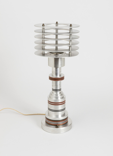 Table lamp composed of stepped, cylindrical metal base decorated with painted and inlaid brass narrow, horizontal bands. Surmounted by shade composed of six flat horizontal metal bands, separated from one another by metal rods. *Note: does not have circular frosted-glass diffuser