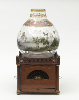 Square wooden box-type cage (a) cut on each side with fan-shaped opening inset with metal wires; quarter columns at corners; bun feet; gallery along top, decorated with circular cutouts and ball finials at corners; stamped gilt-metal decorations at fan-shapes and capitals and bases of columns.  On top of box, cradled in large circular hole with flange, is a globular fishbowl (b) with circular neck and central hollow globe, all formed from single wall (allowing bird entry/egress from and to wooden cage below).  Base of bowl decorated with polychrome enamel band of landscape / water scenes showing European men hunting birds or fishing (retrieving birds?) from boats / sailing ships at sea (one flying two red, white and blue Dutch flags), and a rocky island with a tall castle-like building on top; floral decoration just below neck, gilded foliate decoration on neck and band at mouth.