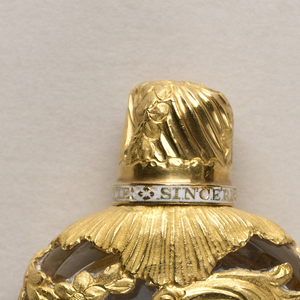 Perfume bottle/scent container composed of a cage-like foil made up of scrolls and plant forms over a crystal bottle.