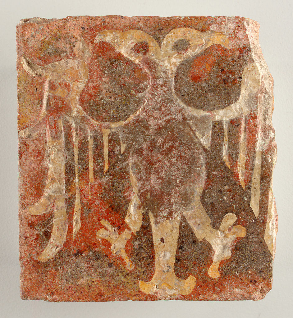 Square tile of red clay, stamped and inlaid with pipe clay in shape of double-headed.  Right edge missing. Four circular pits on back.