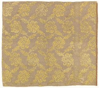 Woven textile showing a yellow floral pattern on a metallic ground.