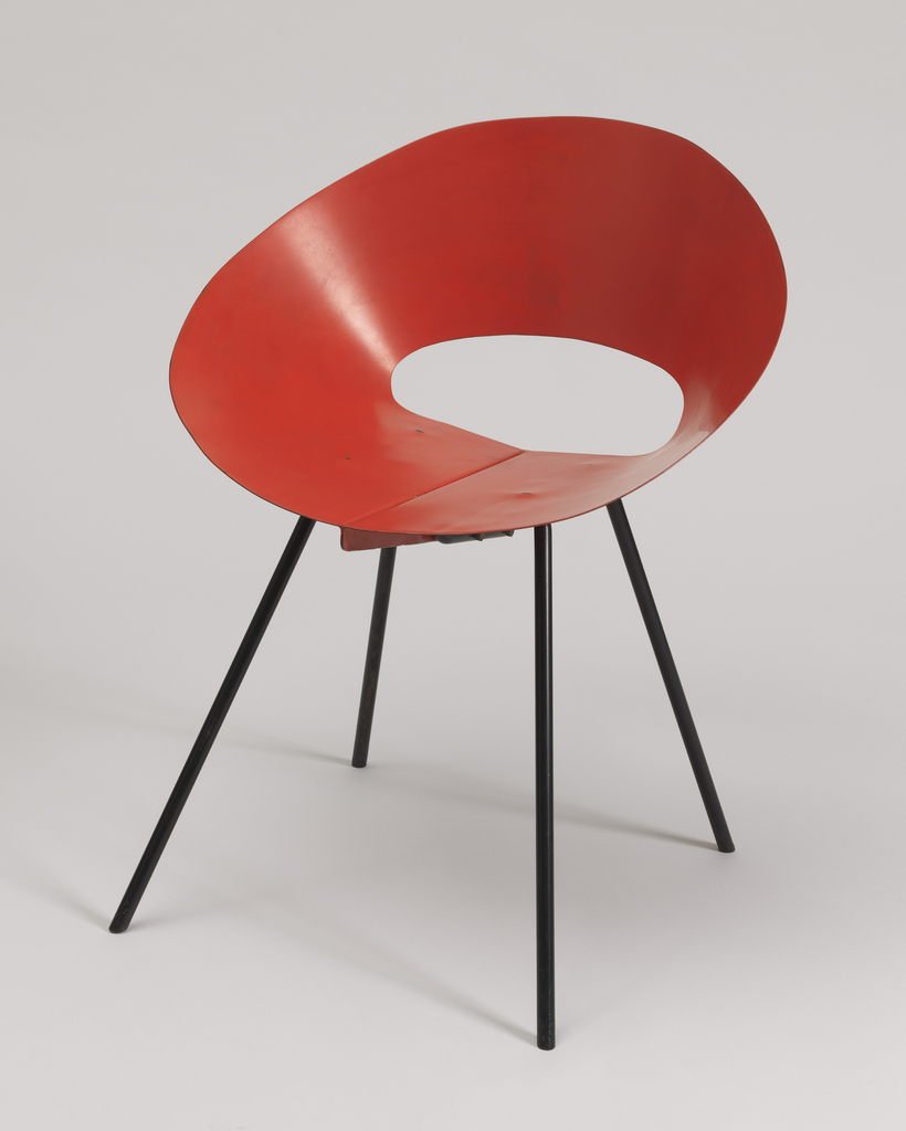 Chair with curved seat cut from sheet metal and four legs of tubular steel.