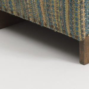 Rectangular form, the base (a) on two copper-surfaced runners; shallow rectangular cushion on top; cushion (b) and base upholstered in coarsly woven blue to tan striped textile.