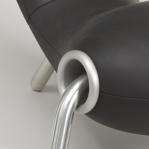 Continuous bulbous seat/back unit thickly padded and covered in black neoprene; the form raised on three splayed tubular aluminum legs with circular aluminum flanges at joints of seat and legs.