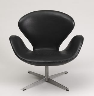 Back, seat and arms formed from trefoil-shaped shell covered in black leather, on aluminum pedestal base with four horizontal feet.