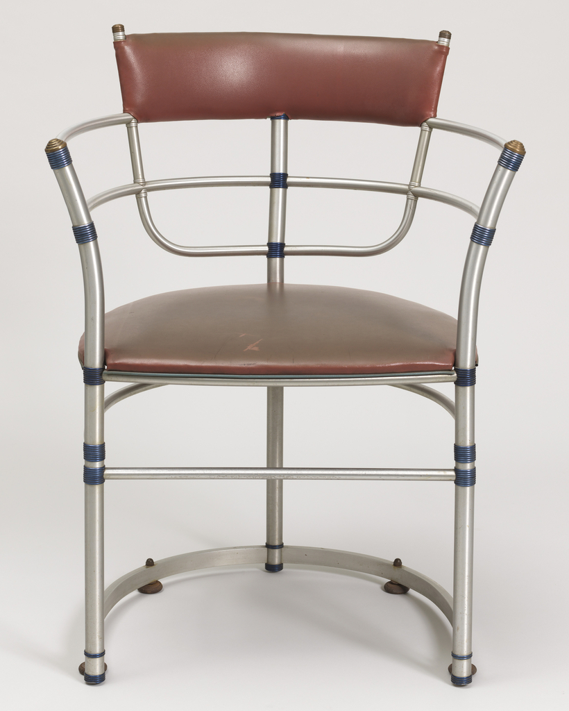 Curved tubular aluminum frame, the joints with aluminum ring connectors; narrow  horizontal back panel and seat covered in brown vinyl.
