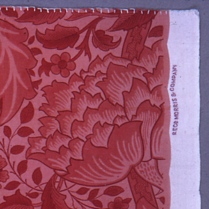 Interlacing stems with alternating conventionalized pomegranate and lotus blossoms, printed in red on a pink ground.
