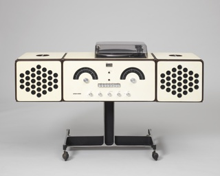 """Radio-phonograph consisting of three main components: a rectangualr, white plastic-laminated plywood body (a) on black inverted T-form base with four casters, the front with controls arranged to suggest a human face, its """"eyebrows"""" represented by arched tuning scales, the """"eyes"""" being the AM and FM dials, the """"teeth"""" a row of square push buttons, and the """"chin"""" a row of circular knobs. Two square white speakers (b,c) as """"ears"""", the fronts pireced with a series of circular holes, sit on the main body, and can be removed to reveal a turntable under a clear acrylic cover. Speakers can be hung from brackets on the sides of the main body, or sit separately from it."""