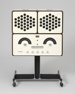 "Radio-phonograph consisting of three main components: a rectangualr, white plastic-laminated plywood body (a) on black inverted T-form base with four casters, the front with controls arranged to suggest a human face, its ""eyebrows"" represented by arched tuning scales, the ""eyes"" being the AM and FM dials, the ""teeth"" a row of square push buttons, and the ""chin"" a row of circular knobs. Two square white speakers (b,c) as ""ears"", the fronts pireced with a series of circular holes, sit on the main body, and can be removed to reveal a turntable under a clear acrylic cover. Speakers can be hung from brackets on the sides of the main body, or sit separately from it."
