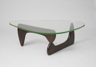 Triangular clear glass top with curved edges on V-form dark wood base composed of two flat, abstract legs.