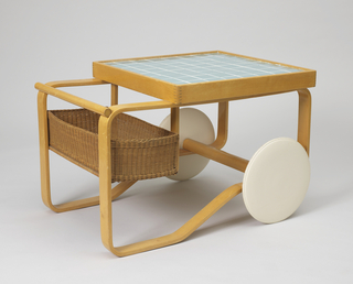 Bent laminated birch strip frame with a horizontal rod handle above a rectangular woven wicker basket; two large circular white-painted wheels at front; square birch-framed top, the surface covered with square green-glazed ceramic tiles.